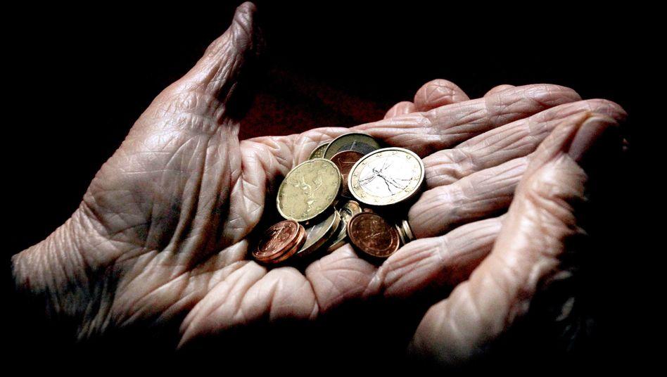 Eine Seniorin hält verschiedene Euromünzen in ihrer Hand