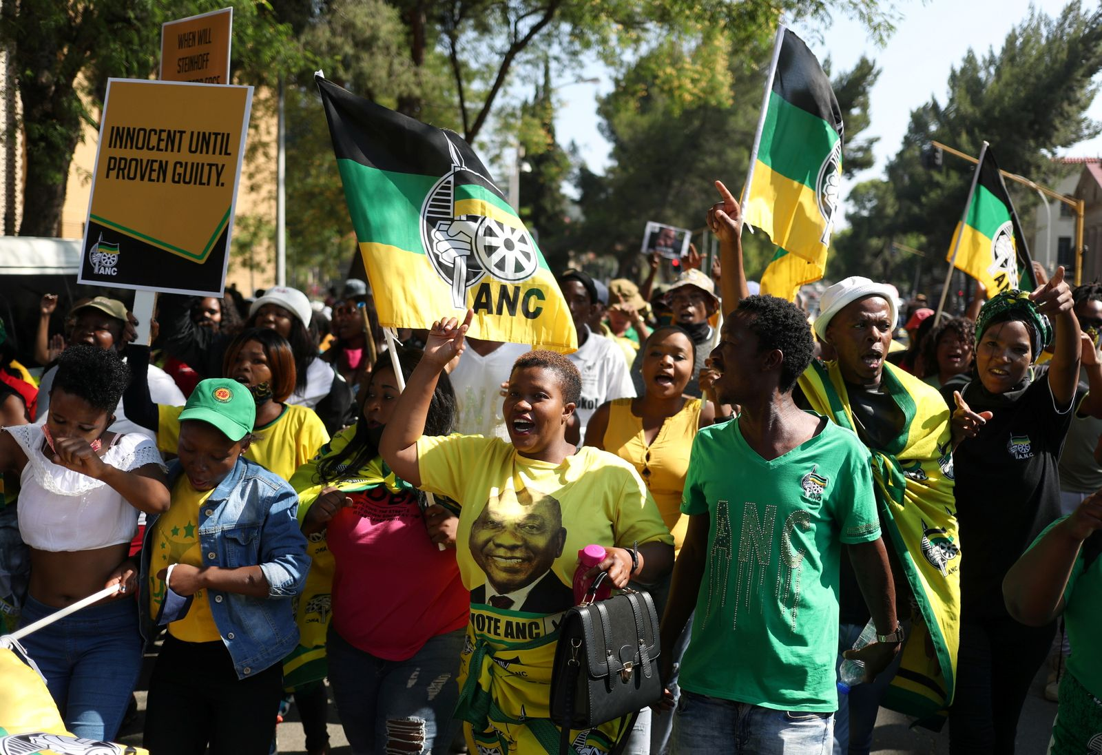 ANC supporters carry placards and flags ahead of the court appearance of Ace Magashule, the secretary general of South Africa's ruling African National Congress, at the Bloemfontein high court in the Free State province