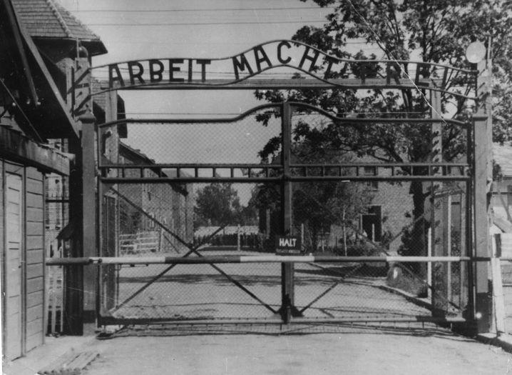 """Dies ist das Tor zum Konzentrationslager Auschwitz. Der Spruch """"Arbeit macht frei"""" hat mit der Wirklichkeit nichts zu tun. Denn normale Arbeit fand in diesem Lager nicht statt. Stattdessen wurden die Menschen durch schwere Arbeit gequält."""