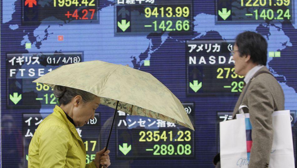 Fußgänger in Tokio passieren eine Börsentafel: Stärkste Abschläge seit Wochen