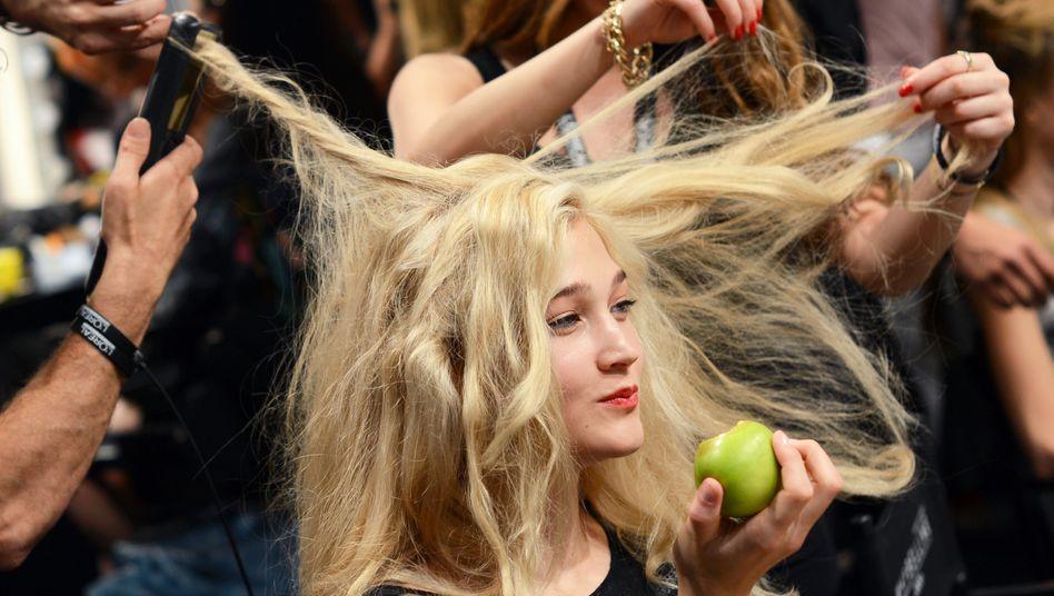 Ein Model wird vor einer Modenschau frisiert (Archivbild)
