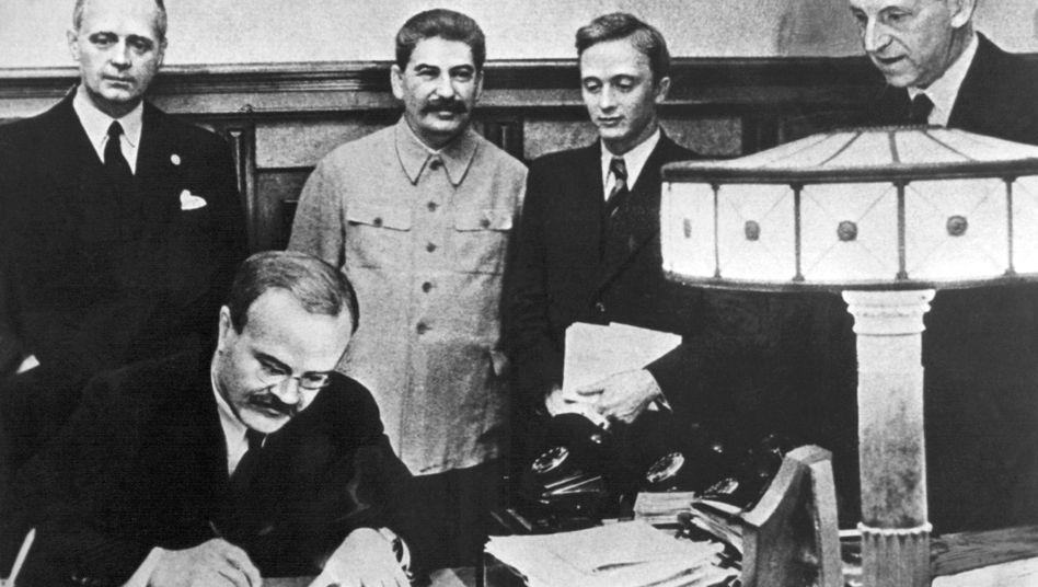 Fatales Bündnis: Im August 1939 unterzeichneten der Außenminister des Deutschen Reiches, Joachim von Ribbentrop (links) und der sowjetische Außenminister Wjatscheslaw Molotow (vorn) den Nichtangriffspakt. Hinten neben Ribbentrop Josef Stalin.