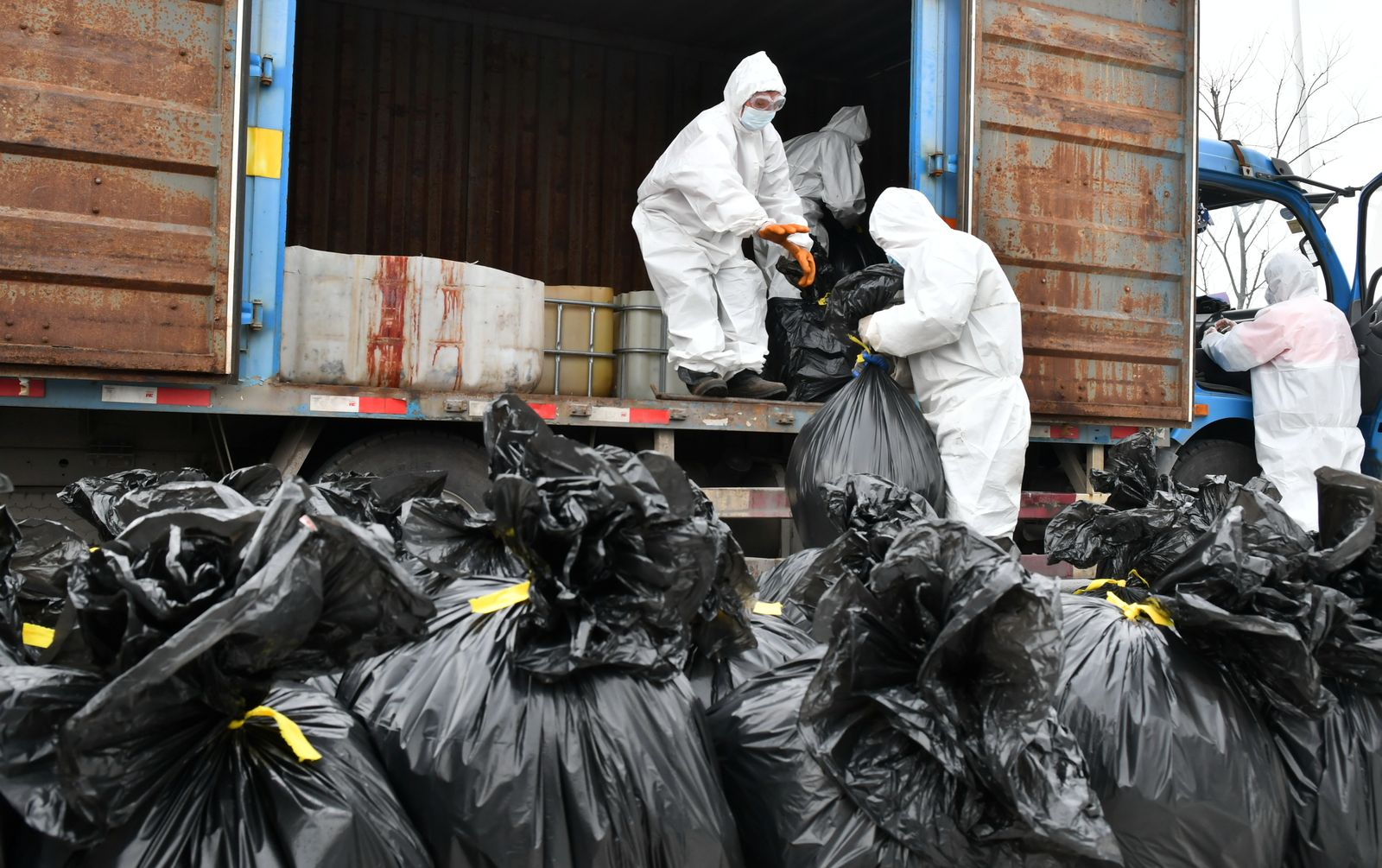Workers in protective suits load household garbage to a truck at a home quarantine medical observation site in Shaoxing