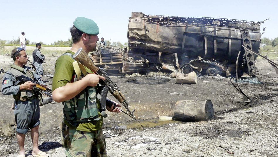 Afghan security forces stand guard near a burnt fuel tanker that had been blasted by a NATO jet.
