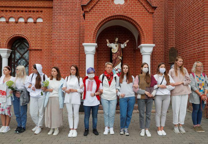 """Protestierende Frauen haben vor der katholischen """"Kirche des heiligen Simon und der heiligen Helena"""" in Minsk eine Menschenkette gebildet"""