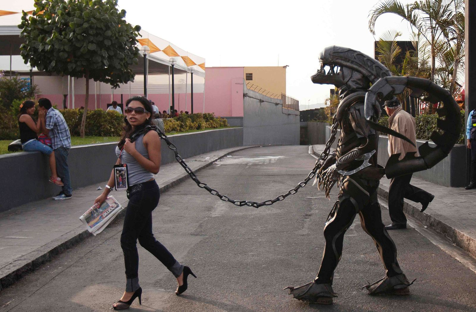 A woman pulls a chain attached to a man, wearing an alien monster costume, as the city of Lima marks the 478th anniversary of its Spanish founding in Lima