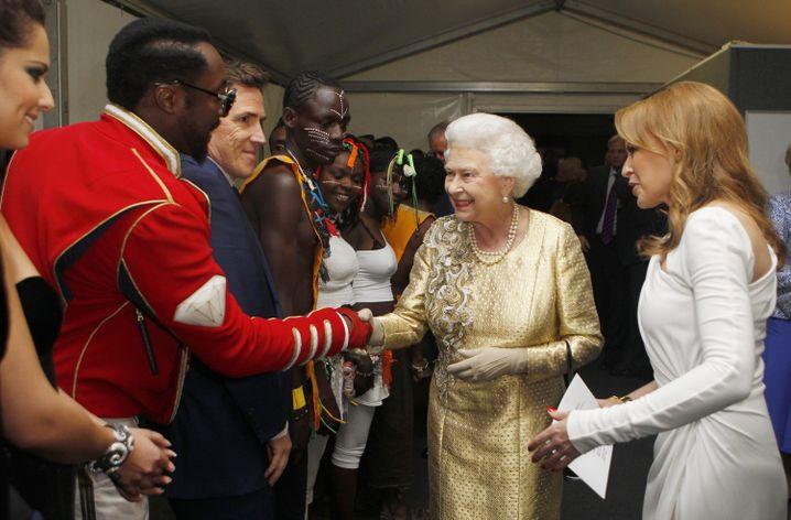 Will.i.am und Queen Elizabeth II. (mit Kylie Minogue) 2012 im Buckingham Palast