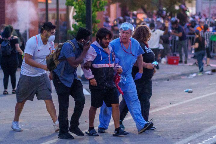 Helfer stützen einen nach Zusammenstößen mit der Polizei verletzten Mann