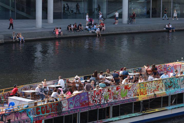 Ausflügler fahren mit einem Boot auf der Spree in Berlin