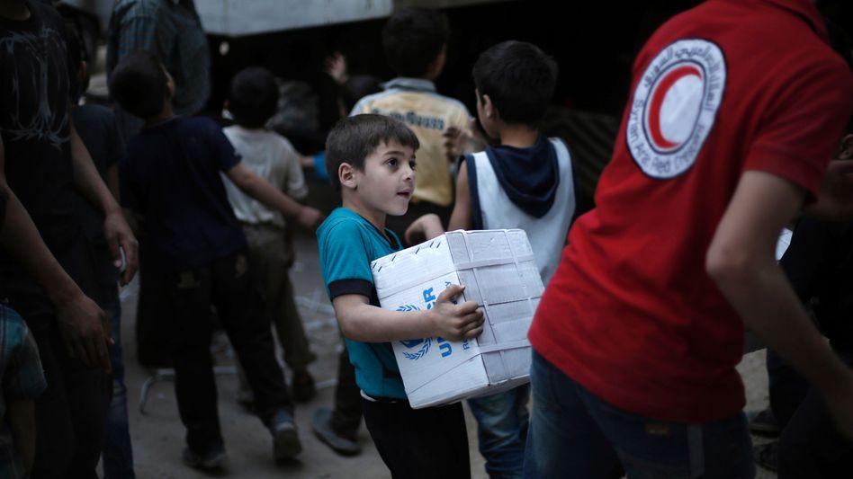 Kinder helfen beim Entladen eines der seltenen Hilfskonvois