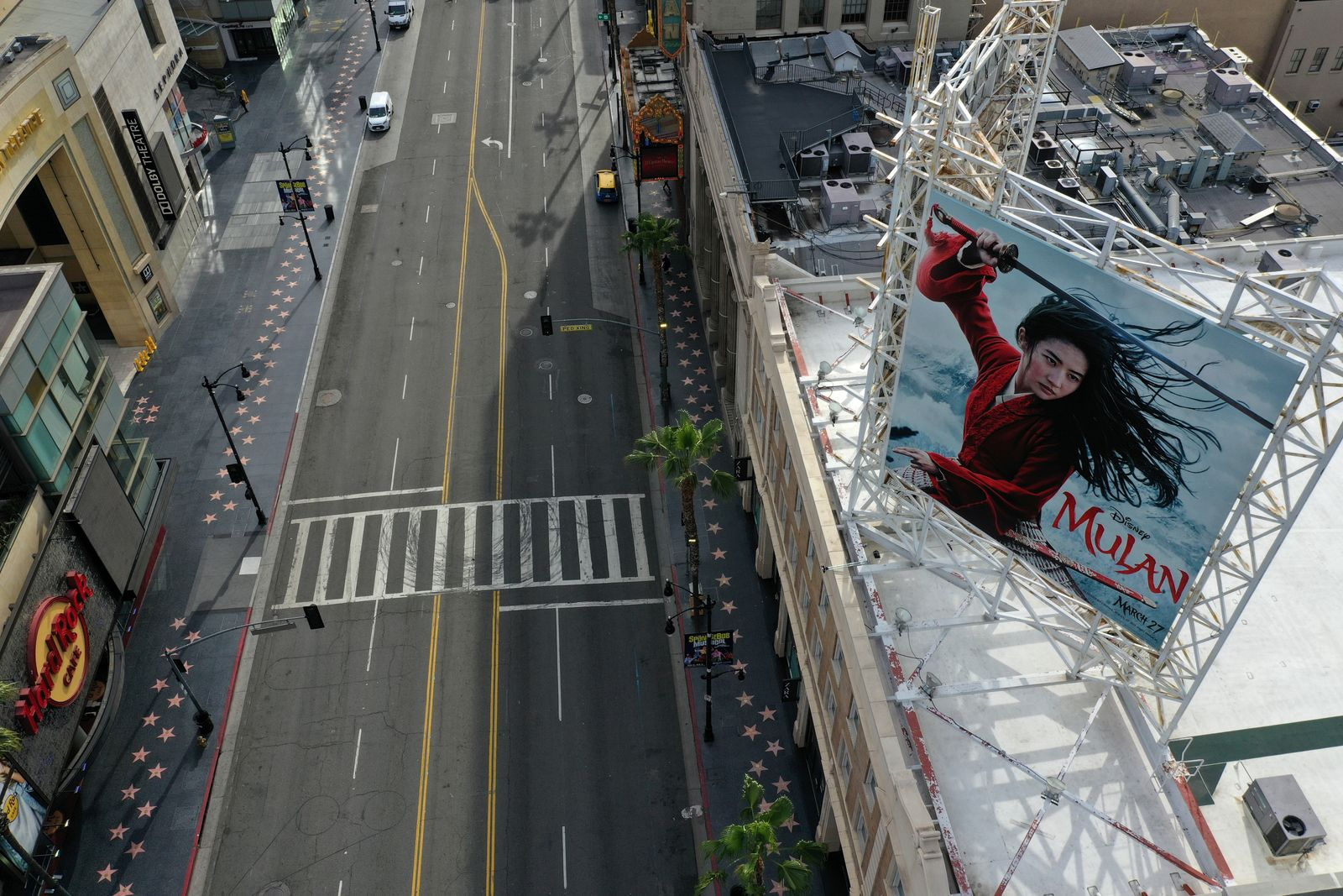 """FILE PHOTO: A poster of the Walt Disney Studios' """"Mulan"""" movie towers over an empty Hollywood Boulevard during the global outbreak of coronavirus disease (COVID-19), in Hollywood, Los Angeles"""