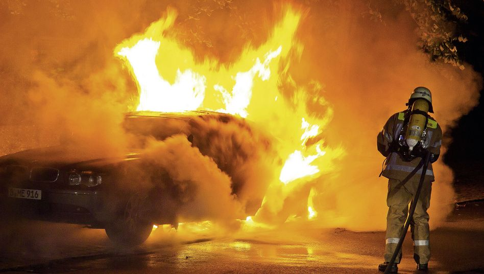 Fire fighters extinguish a blazing car in Berlin, one of hundreds set set on fire this year.