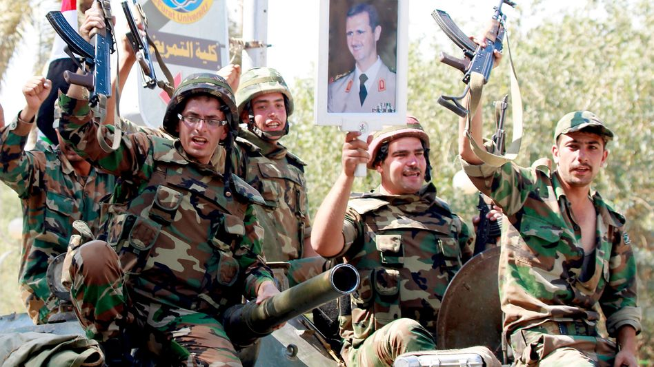 Syrian soldiers raise their weapons while holding a picture of Syrian President Bashar Assad in the city of Deir el-Zor in August.