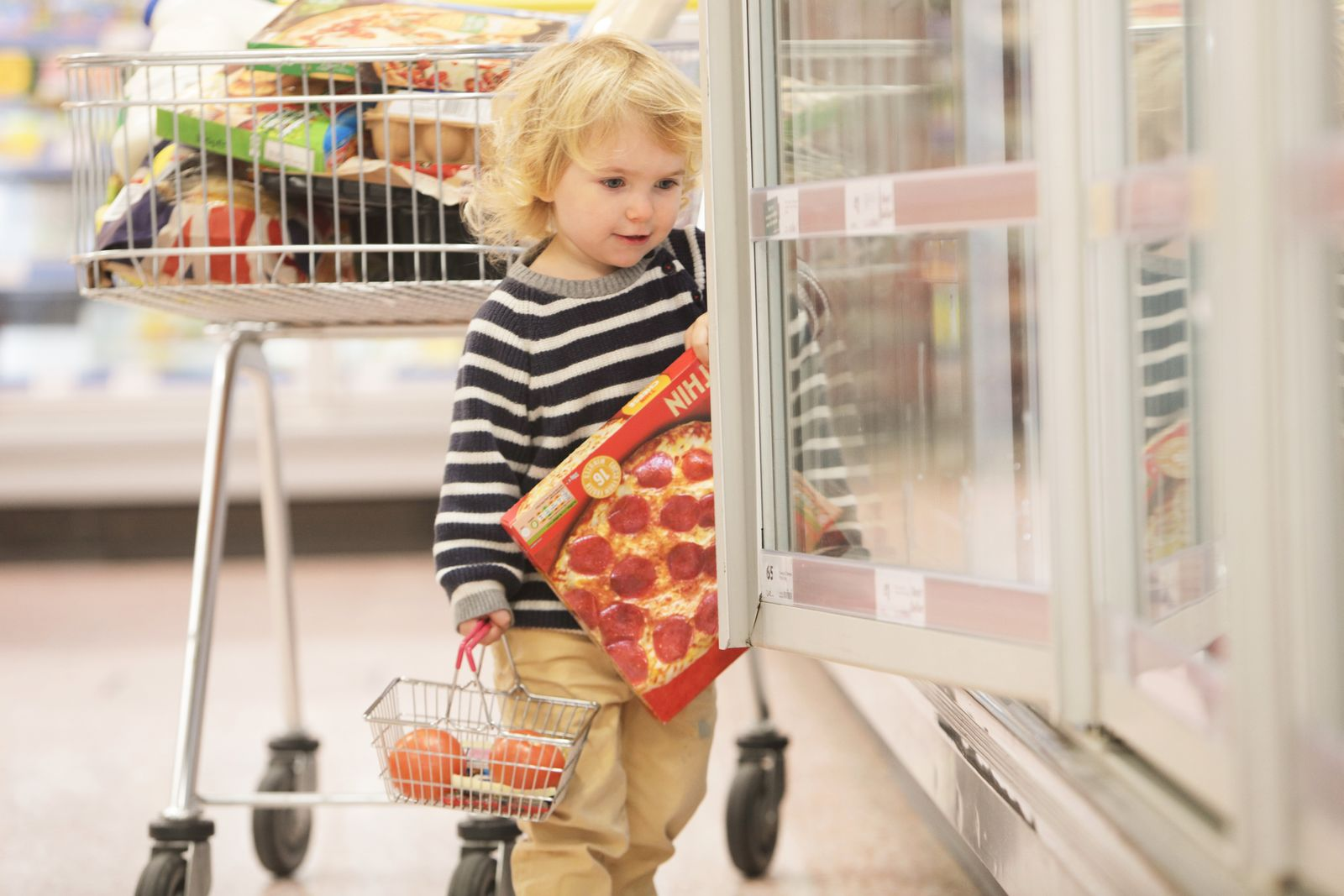 Toddler choosing pizza in supermarket