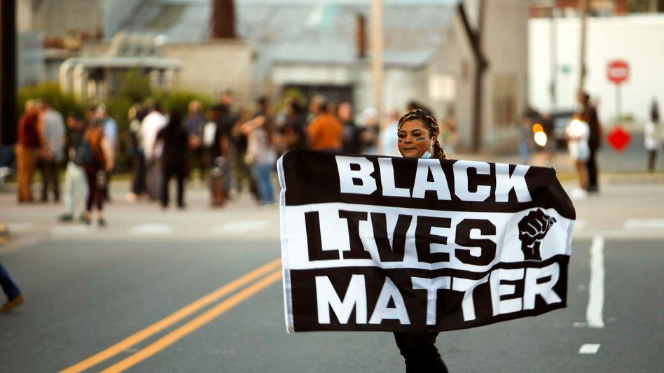Eine Demonstrantin hält eine »Black Lives Matter«-Fahne in die Höhe