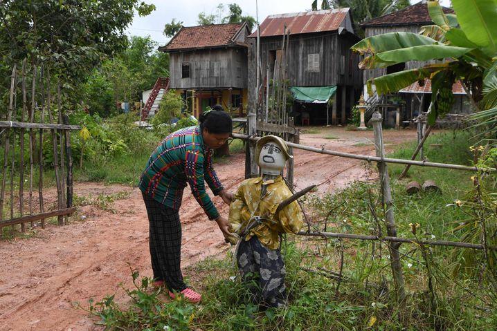 """Eine Frau richtet vor ihrem Haus in der kambodschanischen Provinz Kampong Cham eine Figur her, die in der Region als """"Ting Mong"""" bekannt ist und das Coronavirus abhalten soll."""
