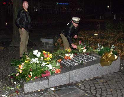 Nach der rechtsextremen Randale: Ein Polizist legt Blumen zurück auf den Gedenkstein.