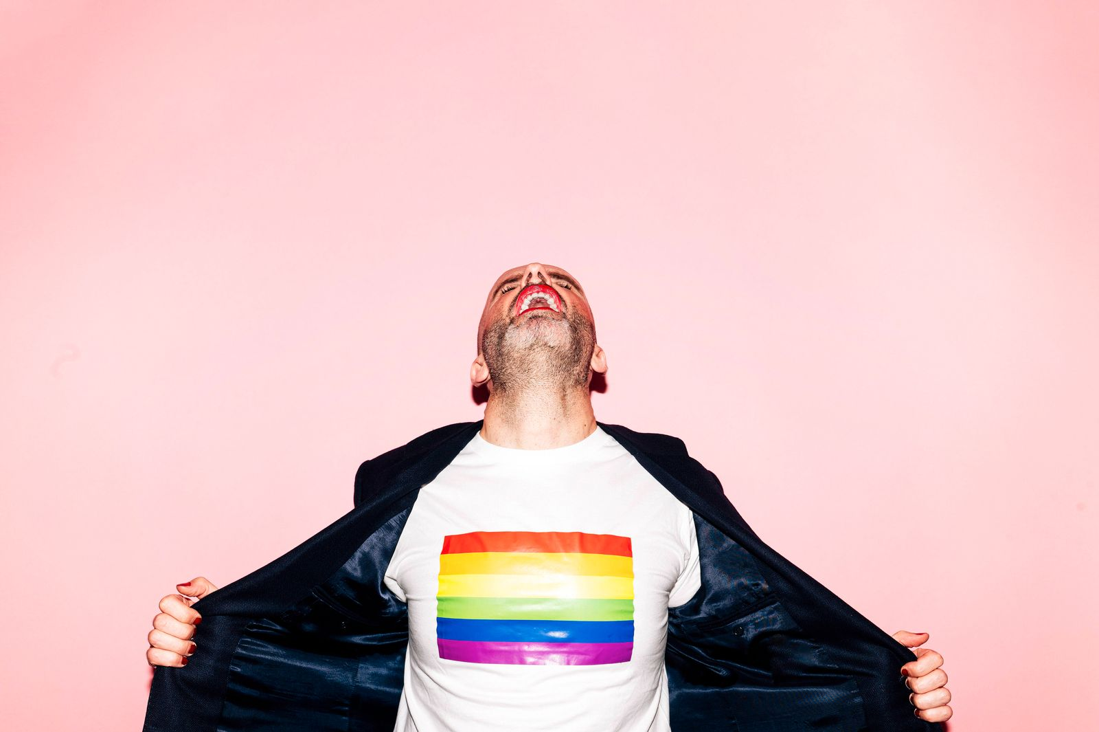 Confident bearded man with red lips screaming and demonstrating LGBT flag on white t shirt against pink background Copy