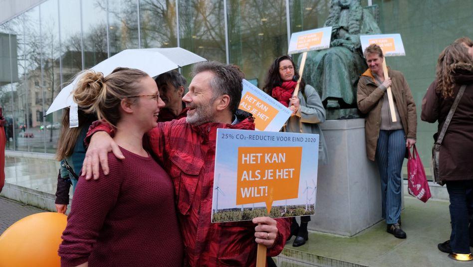 Klimaaktivisten feiern vor dem Gerichtsgebäude in Den Haag