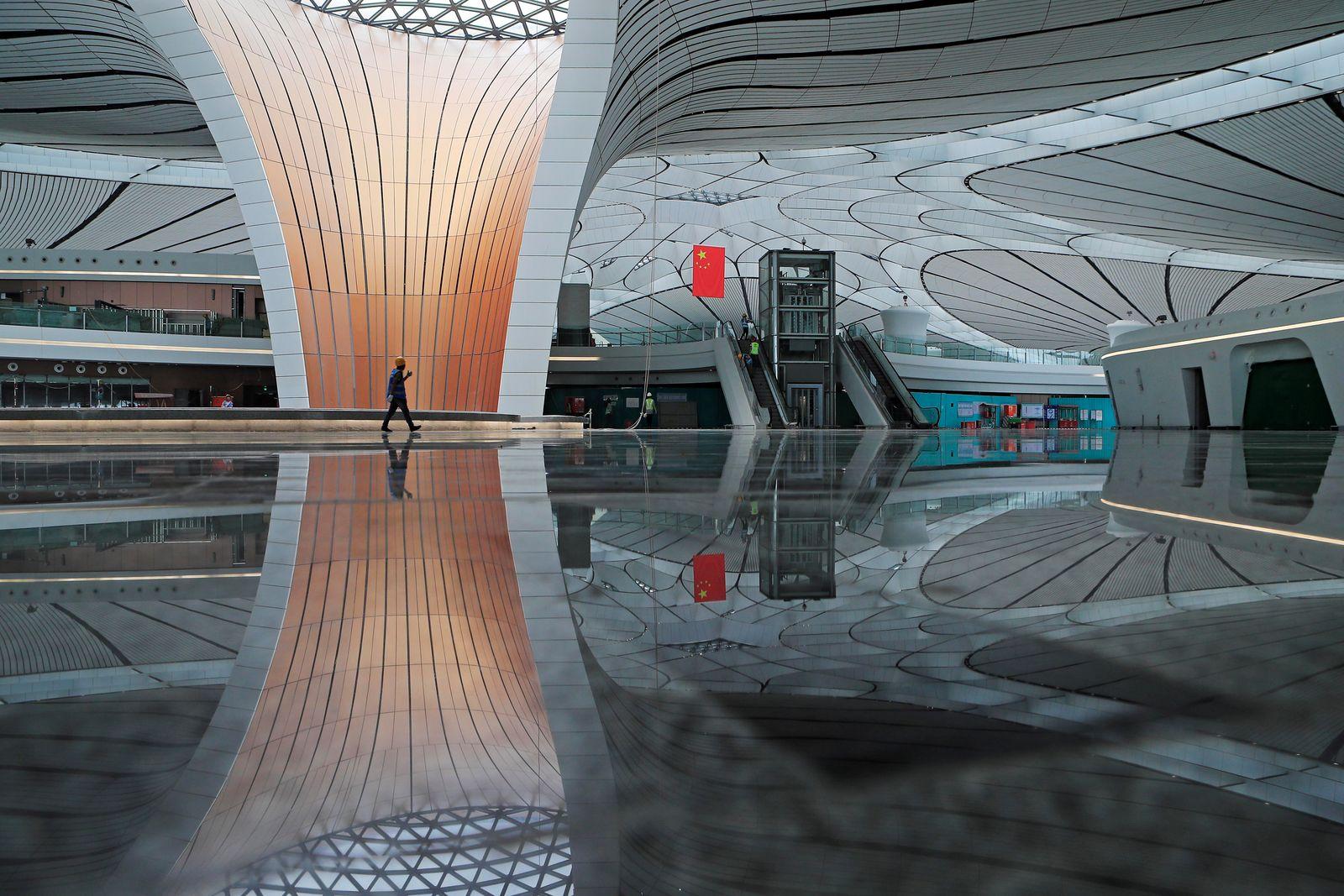 Worker walks inside the terminal hall of the Beijing Daxing International Airport under construction in Daxing district, Beijing