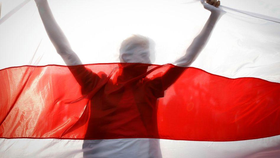 Ein Demonstrant hinter einer historischen belarussischen Fahne