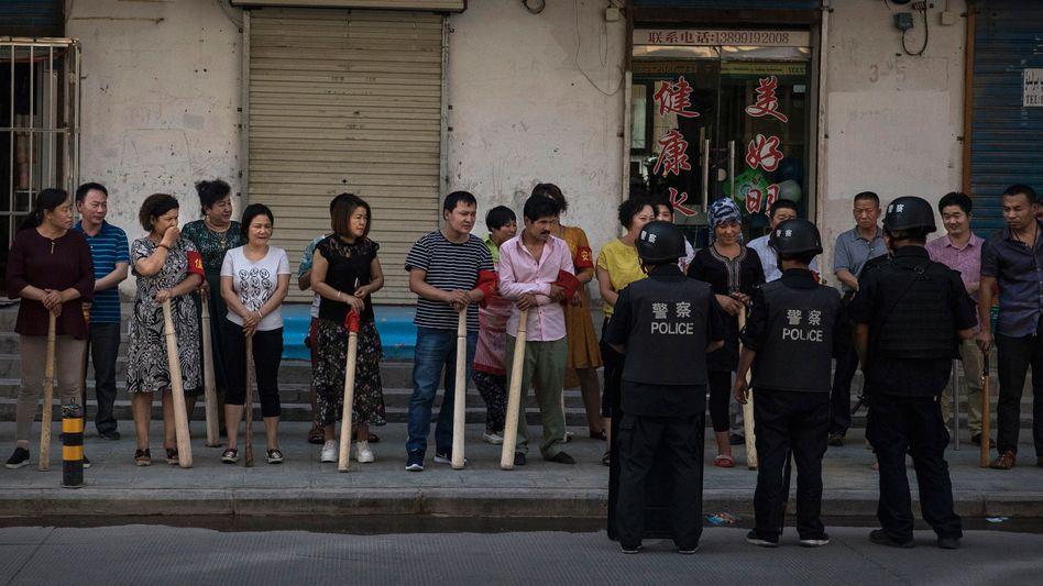 In der Provinz Xinjiang stehen Uiguren und Han-Chinesen auf der Straße