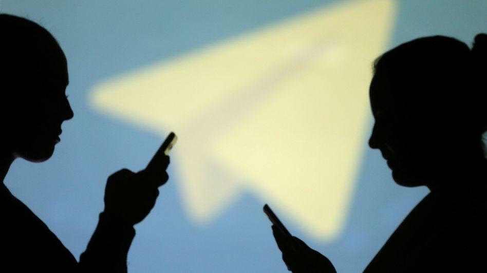 Smartphone-Nutzer vor dem Logo von Telegram