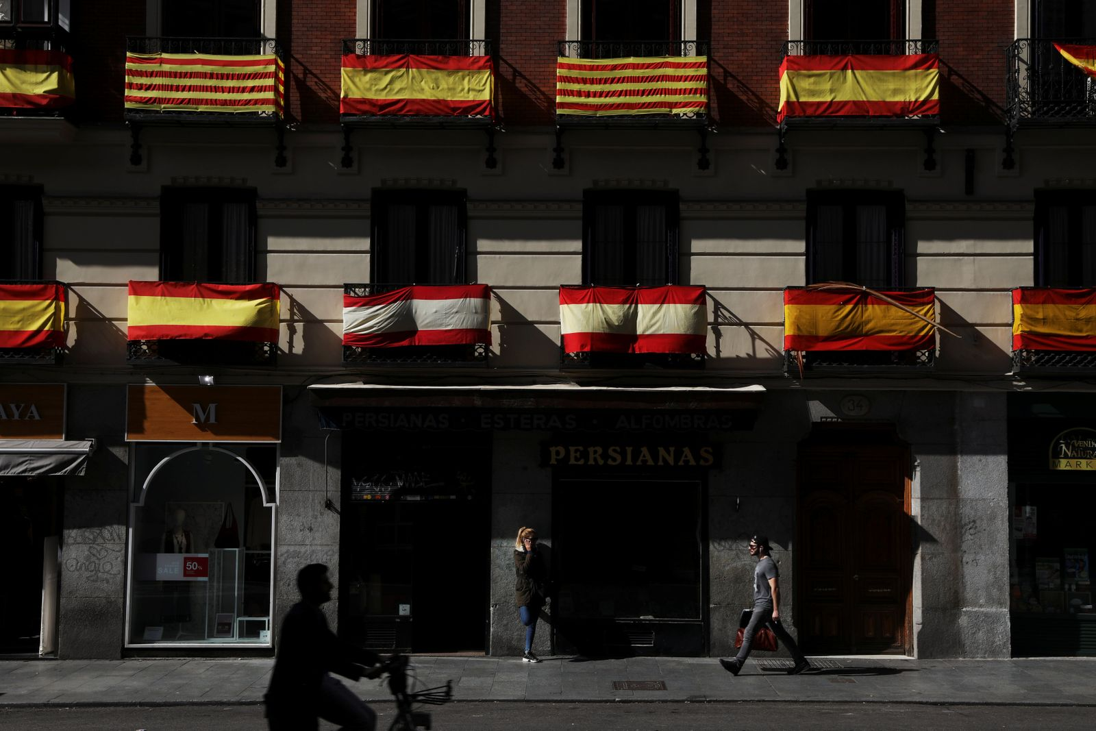Spanish and Catalan flags hang from balconies in Madrid