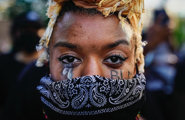 A woman with the letters BLM on her face, which stands for Black Lives Matter.