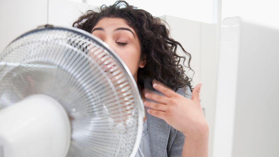 Frau vorm Ventilator: Trifft kalte Luft auf den Hals, sinkt die Temperatur in der Rachenschleimhaut, wovon Viren profitieren