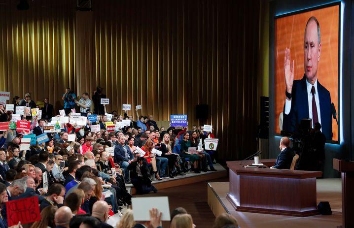 Zuschauer stellen auf Schildern Fragen an Wladimir Putin
