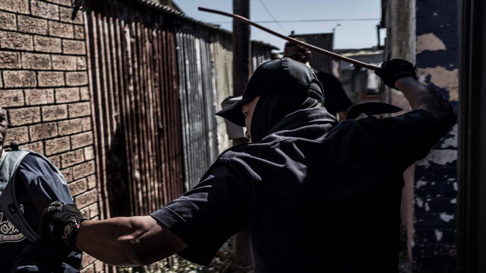 Ein Polizist in Kapstadt setzt die Ausgangssperre mit Gewalt durch
