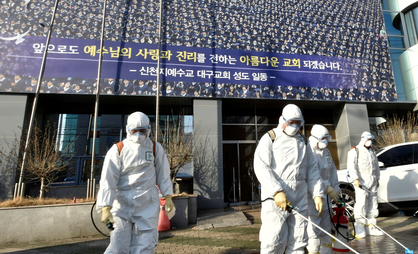 """Workers from a disinfection service company sanitize a street in front of a branch of the Shincheonji Church of Jesus the Temple of the Tabernacle of the Testimony where a woman known as """"Patient 31"""" attended a service in Daegu"""