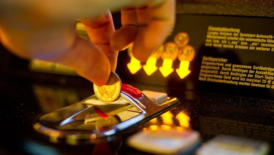 Münzeinwurf beim Spielautomaten: Je schneller das Spiel, desto höher die Spielsuchtgefahr