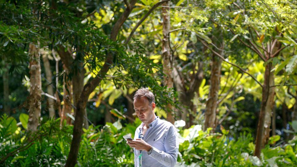 Ein Fußgänger schaut in Singapur auf sein Smartphone - und darf das auch