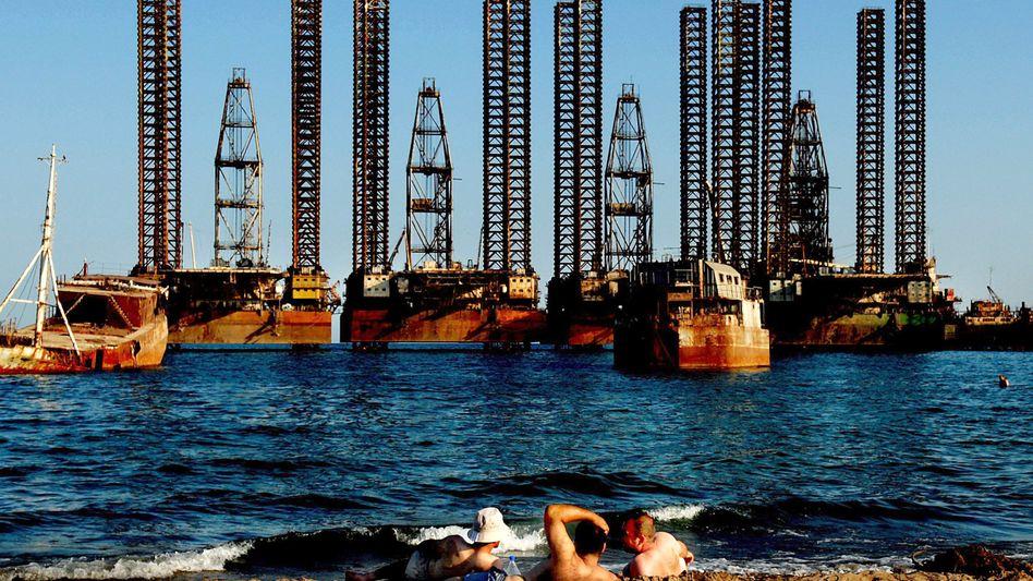 Oil workers in Azerbaijan catching a few rays on the shore near Baku.