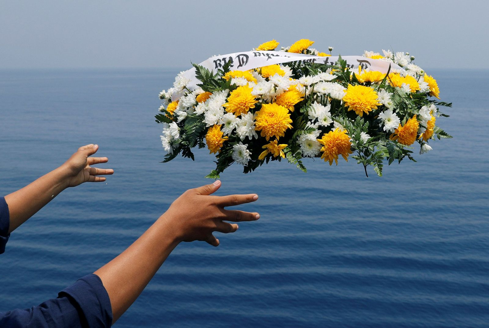 A member of a family of passengers of Lion Air flight JT610 throws a wreath from the deck of Indonesia Navy ship KRI Banjarmasin as they visit the site of the crash to pay their tribute, at the north coast of Karawang
