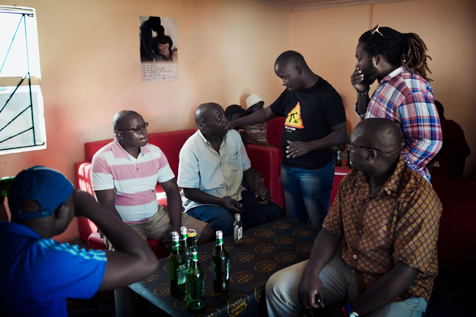 Social worker talks to men in a bar in Mfuleni, South Africa