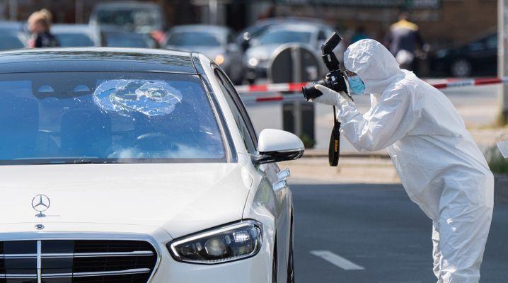 Ein Mitarbeiter im Spurenschutzanzug macht Fotos von einem Wagen in Hannover: Die Hintergründe der Auseinandersetzung sind noch unklar