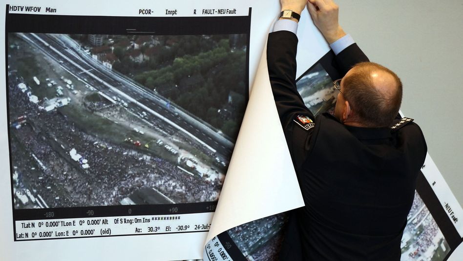 A police official hangs pictures from the Love Parade on the wall ahead of a state parliamentary committee meeting on Wednesday.