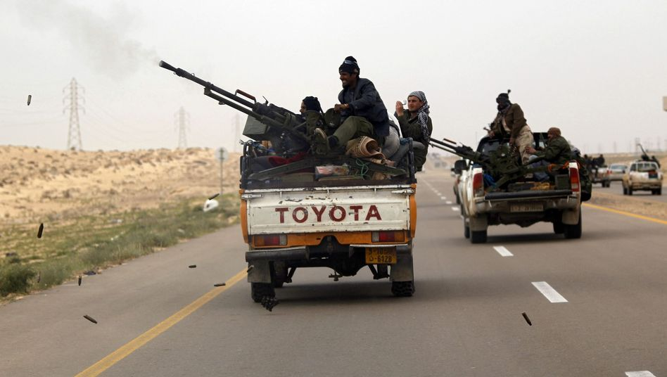 A pick-up truck carrying rebel fighters flees advancing pro-Gadhafi forces near the town of Ajdabiyah on Tuesday.