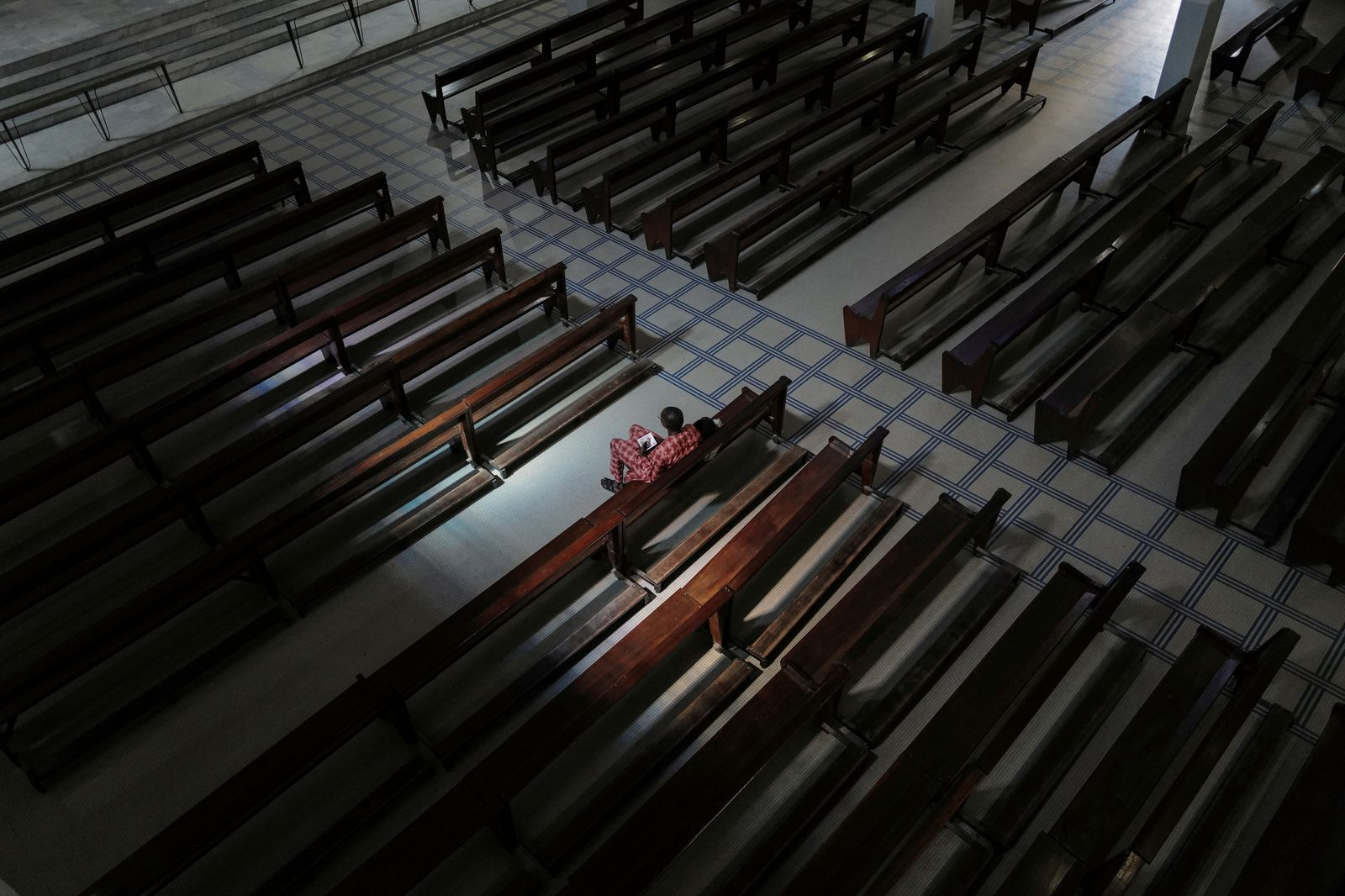 Faithful sits alone at the empty Notre-Dame des Victoires Cathedral during the Sunday mass in Dakar