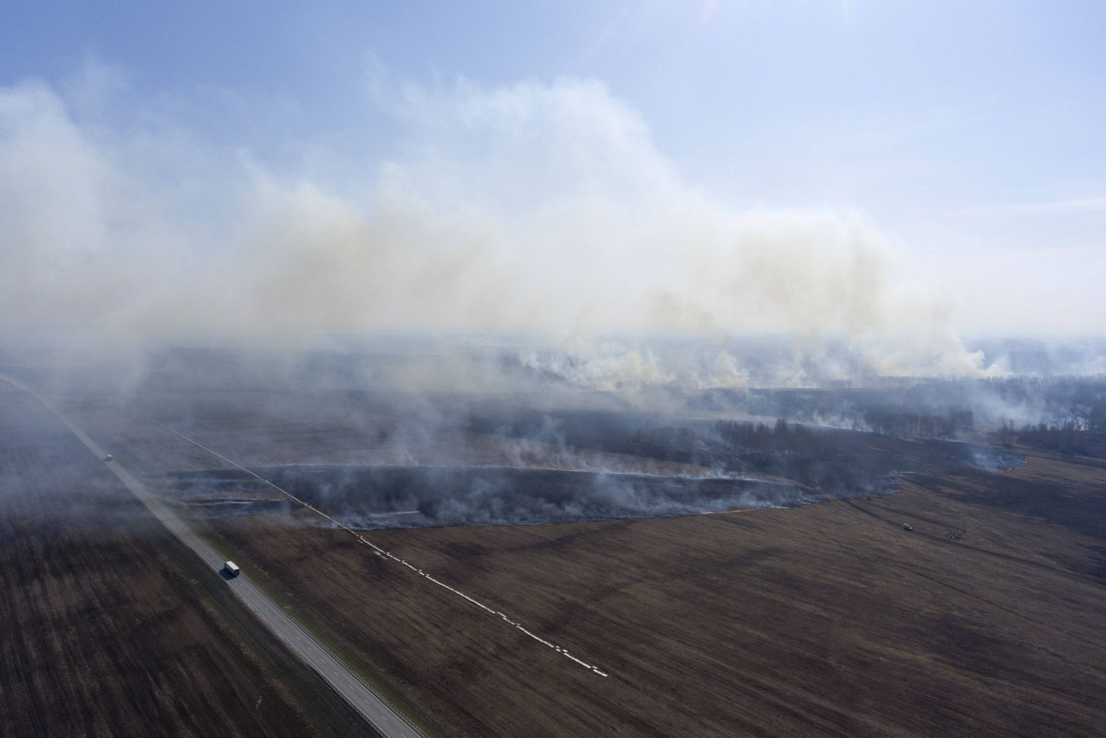 NOVOSIBIRSK REGION, RUSSIA - APRIL 23, 2020: An aerial view of a grass fire in the fields in Bolotnoye District, Novosib