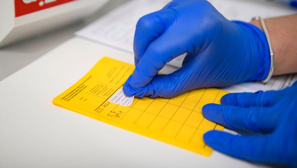 Eintragung in einen Impfpass in einem Impfzentrum in NRW: Eine Fälschung soll 150 Euro kosten