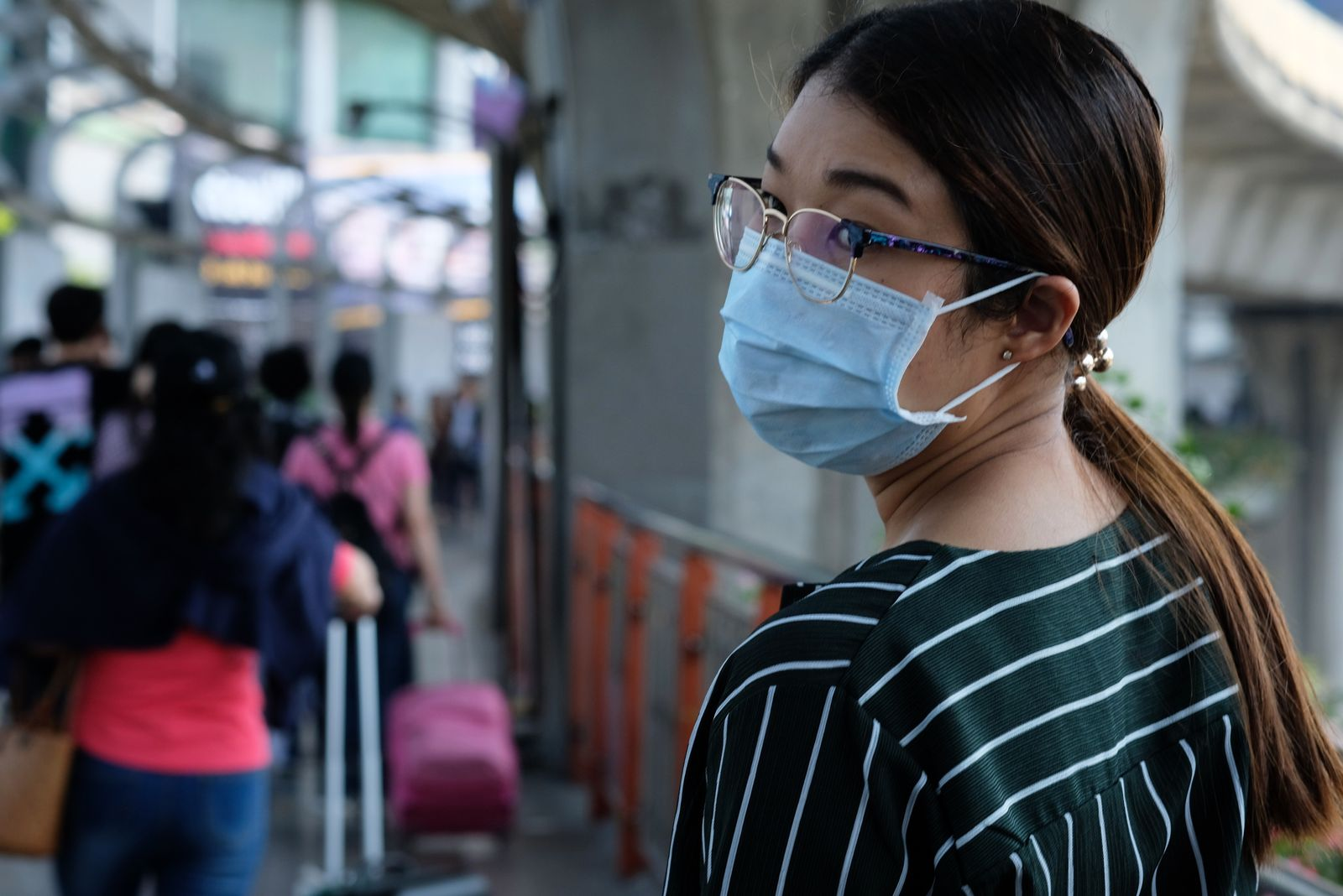 Rear View Of Woman Wearing Flu Mask At Airport