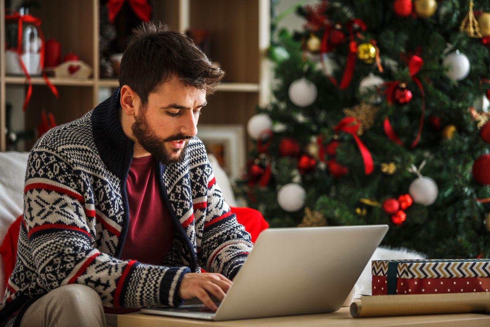 EINMALIGE VERWENDUNG Mann allein Weihnachtsbaum Laptop