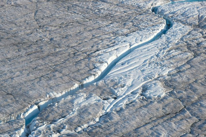 Meltwater carves its way through a Greenland glacier.