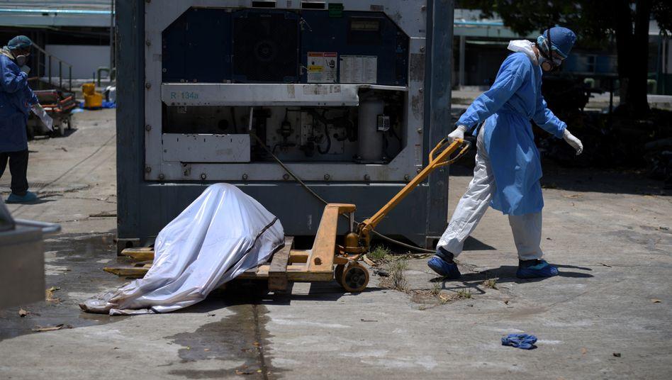 Ein Krankenhausmitarbeiter transportiert in Guayaquil einen Toten, der an Covid-19 gestorben ist: Das Virus breitet sich rasend schnell aus