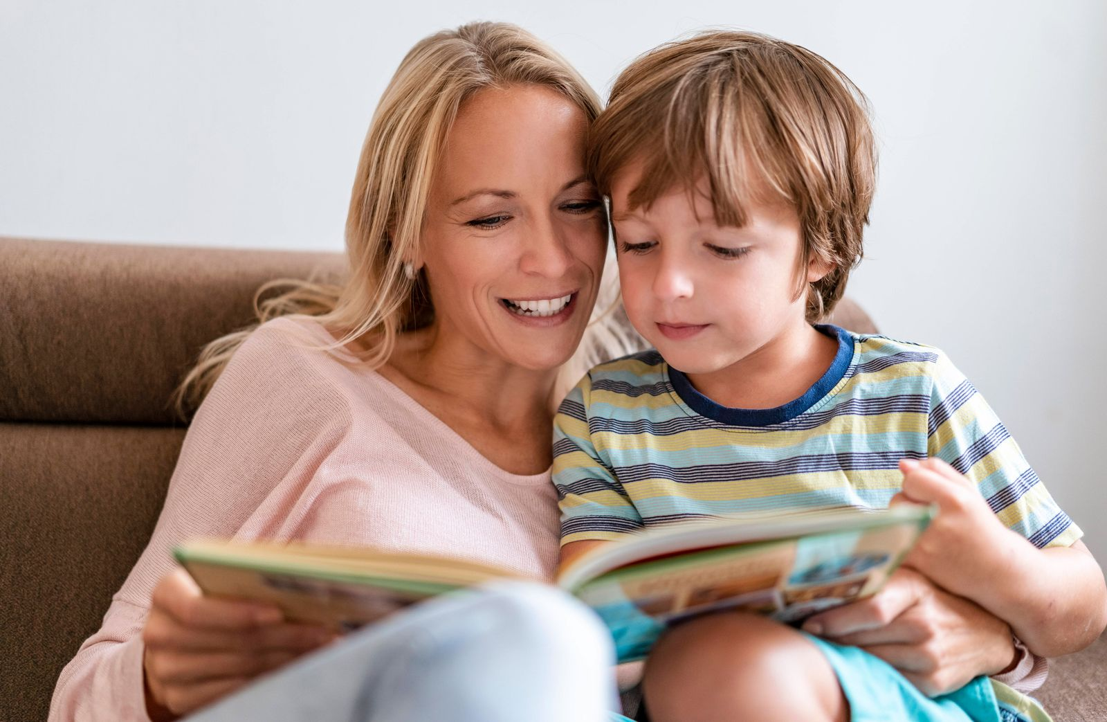 Mother and son reading a book together on couch at home model released Symbolfoto property released PUBLICATIONxINxGERx