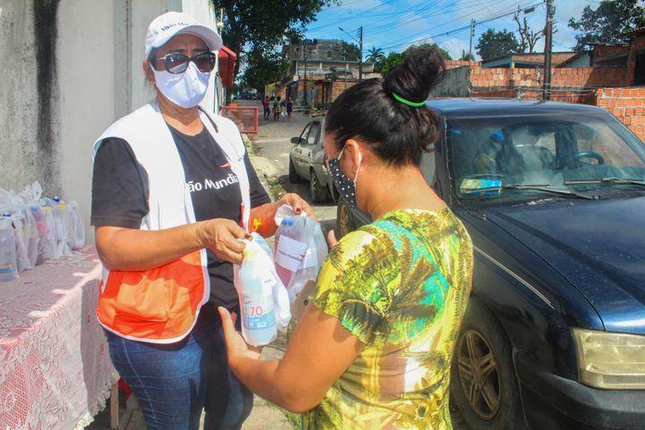 Maria Lucinete Trindade Bezerra (links) verteilt Corona-Schutzpakete mit Produkten wie Desinfektionsmitteln